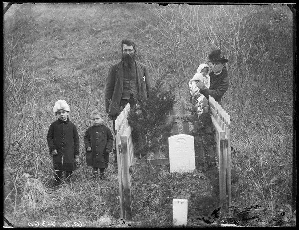 The Harvey Andrews family posed at the grave of son Willie Andrews.