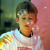 Boy blowing bubbles at Festival