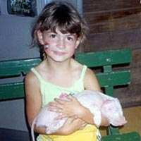 Bayley Rustad holds piglet the Fair's Swine Barn, August 17, 1999