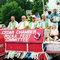 Polka Fest Committee members ride on float while band plays, July 3, 1999