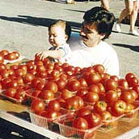 Man with baby looking at tomatoes at Omaha Farmers Market