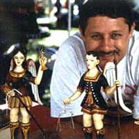 Artist David Nabor Lucero with his painted carved bultos, 1998
