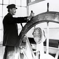 Captain Anthony Meldahl in the pilothouse of the steamboat Queen City