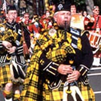 Bagpipers in Scottish regalia march in the Christmas parade