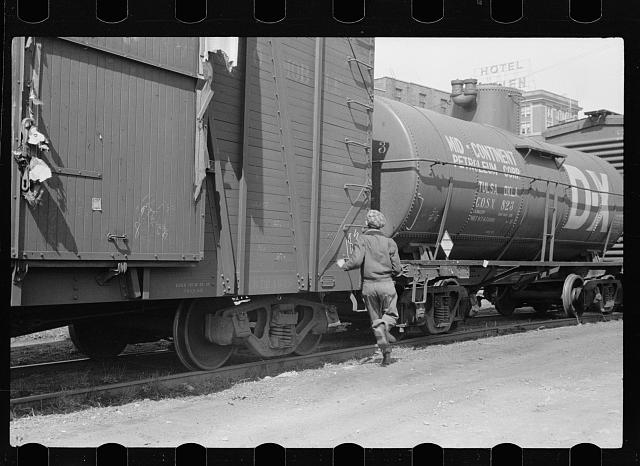 Boy hopping a freight train, 1940, by John Vachon
