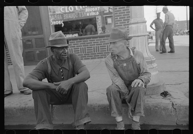 Negro and white man sitting on curb talking