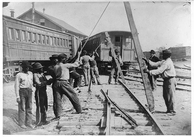 men using levers for loosening rails
