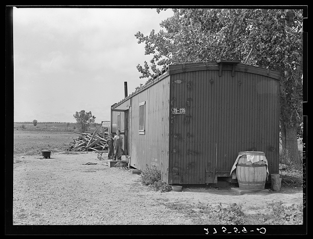 Boxcar home with children at door. Land cleared surrounding boxcar which has a screen door built in and other supplies stored nearby.