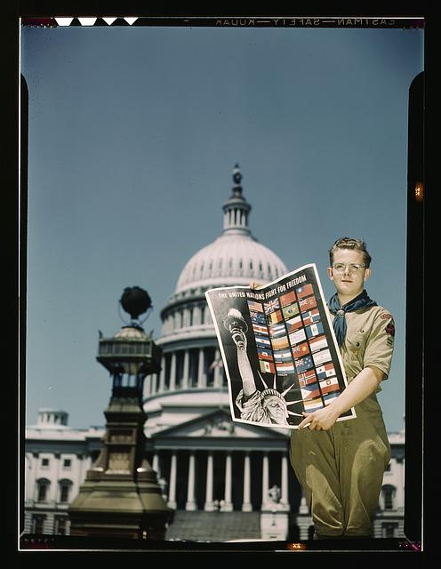 Boy Scout after 1942 showing posters Scouts distributed; photo by John Rous, Library of Congress collection