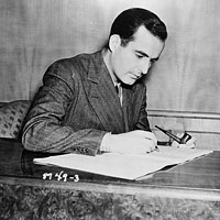 Samuel Barber, seated, making notes on his music
