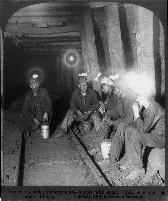 Dinner 2-1/2 miles underground--miners with safety lamp, in a soft coal mine, Illinois