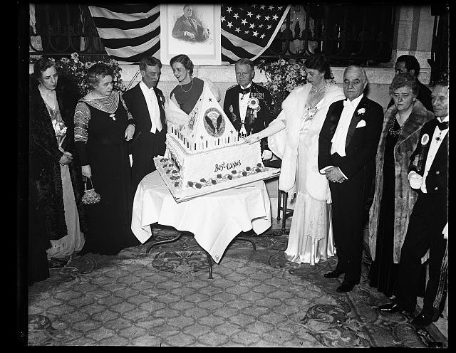 FIRST LADY LIGHTS BIRTHDAY CAKE. MRS. ROOSEVELT LIGHTS THE CANDLES ON THE BIRTHDAY CAKE AT THE SHOREHAM HOTEL BIRTHDAY BALL OF PRESIDENT ROOSEVELT. THE PRESIDENT REMAINED AT THE WHITE HOUSE AND HAD WITH HIM A FEW CLOSE FRIENDS. IN THE ABOVE PICTURE MRS. WOODROW WILSON IS ON THE EXTREME LEFT. DIRECTLY BEHIND THE CAKE IS MRS. CURTIS DALL. MAJ. WILLIAM HORTON IS BETWEEN MRS. DALL AND MRS. ROOSEVELT AND RAYMOND T. BAKER, CHAIRMAN OF THE BIRTHDAY BALL COMMITTEE, IS ON THE RIGHT OF THE PICTURE